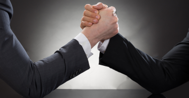 stock-photo-close-up-of-a-two-businessman-competing-in-arm-wrestling-282607136
